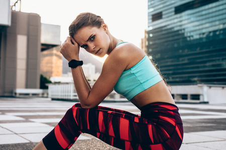 Portrait of young woman sitting outdoors with serious expression. Athletic woman relaxing after intense workout. Stock Photo - 100844154