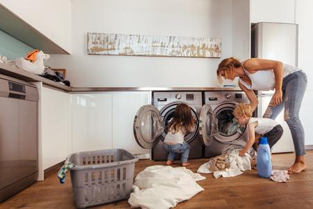 Mujer con niños carga ropa en lavadora. Madre e hijos poniendo ropa en la lavadora en casa.