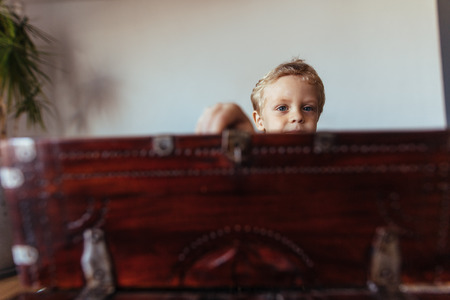 Small boy at home opening an old wooden box. face of little boy behind old trunk. Archivio Fotografico