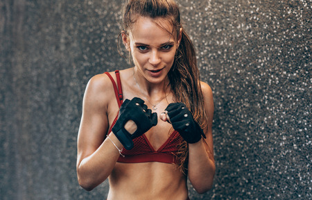 Female wearing gloves ready to fight. Woman boxer exercising outdoors against grey wall.