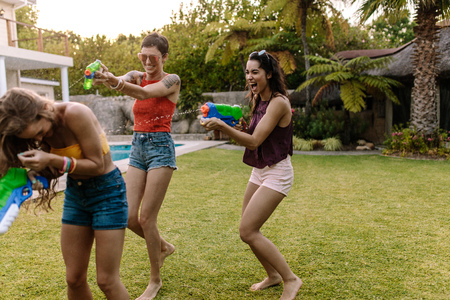 Group of female friends outdoors having fun playing with water guns. Women at pool side playing with water pistols. Stock Photo