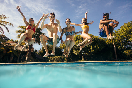 Group of multi-ethnic young people looking happy while jumping into the swimming pool together. Friends enjoying pool party. Stock Photo