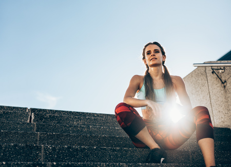 Health young woman sitting on stairs outdoors in morning. Female athlete taking rest after workout with sun flare. Imagens - 101090157