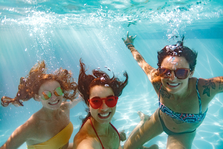 Happy young women friends swimming underwater in pool. Underwater shot of smiling females in pool taking selfie.