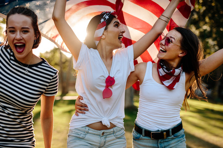 Three young female friends with American flag having fun in the park. Smiling group of women celebrating 4th of july outdoors.