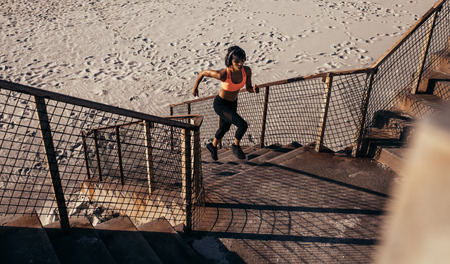 Athletic woman runs up the steps on the beach. Athlete in sportswear training on concrete steps.
