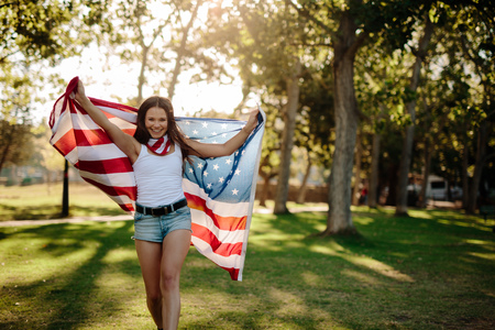 Beautiful young woman walking in the park and waving American flag. Smiling girl with American flag at park.