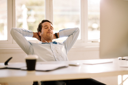 Businessman relaxing at home sitting in front of his work table. Man taking a break and listening to music using earphones with eyes closed.