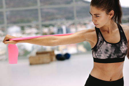Health conscious woman exercising with resistance band at fitness studio. Female in sportswear doing arms stretching workout with resistance band.