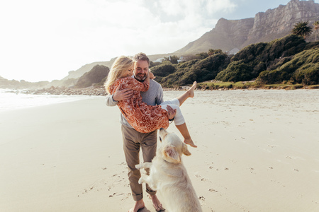 Handsome mature man carrying his wife in his arms on the beach with their pet dog in front. Romantic senior couple with a dog on sea shore. 版權商用圖片