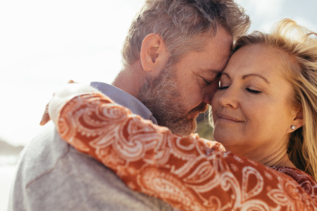 Affectionate senior couple embracing outdoors on beach. Beautiful mature woman being embraced by her loving husband on the beach.
