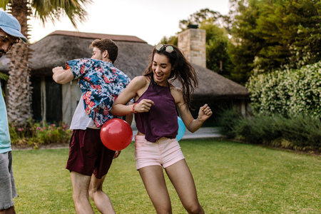 Woman trying to pop a balloon with her hips tied on mans back. Friends playing balloon popping games at party outdoors. Stock Photo