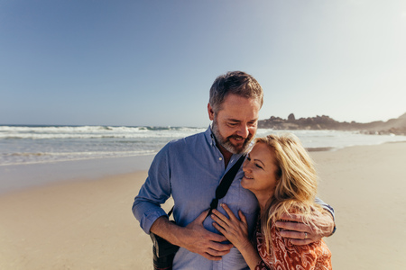 Portrait of romantic mature couple spending time together on the beach. Happy senior man embracing with his wife on the sea shore.