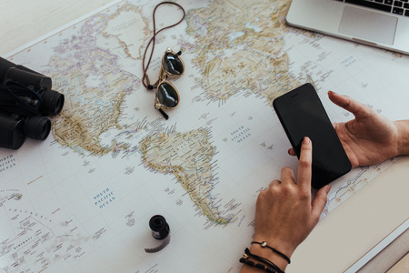 Woman hand using smart phone with a world map on table. Point of view of female tourist planning vacation with travel accessories around.