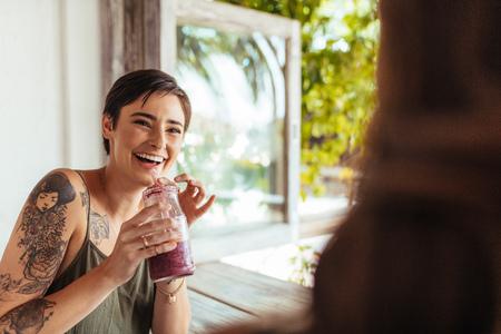Femme tenant un pot de smoothie parlant à son amie dans un restaurant. Femme avec tatouage sur place dans un restaurant, boire du jus.