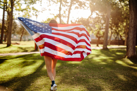 Young woman holding American flag and running in the park. Girl carrying American flag while running through a park on summer day. Celebrating fourth of july.