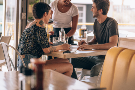 Young couple sitting at cafe giving order to a female waiter. Man placing order to a waitress at restaurant while sitting with his girlfriend.