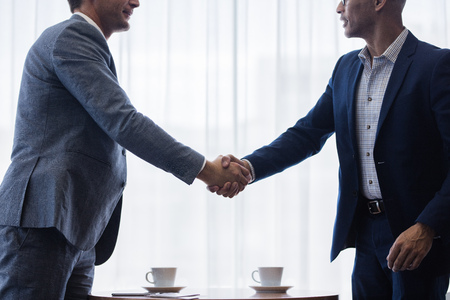 Two business men shaking hands with each other after a deal. Businesspeople shaking hands making a necessary agreement during a meeting.