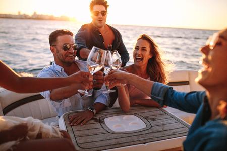 Jóvenes en yate bebiendo juntos. Grupo de amigos brindando bebidas y fiesta en barco.