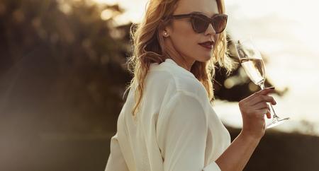 Attraktive Frau in der Sonnenbrille, die Wein draußen trinkt. Schöne Frau, die ein Glas Wein hat, das rückwärts schaut.