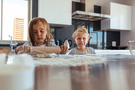 Innocent little girl with rolling pin and boy crying in kitchen. Little kids baking cookies in kitchen.