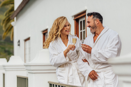 Beautiful couple in bathrobe clinking glasses of wine and smiling. Cheerful couple wearing bathrobes with glasses of champagne in luxury villa.
