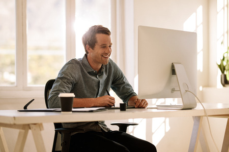 Smiling businessman working on computer with a coffee glass on table. Smiling man sitting at his work table working on computer. Banco de Imagens