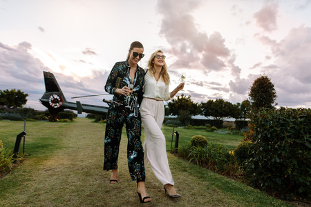 Full length of two young women walking together with a helicopter parked in background. Stylish females enjoying a luxurious lifestyle.
