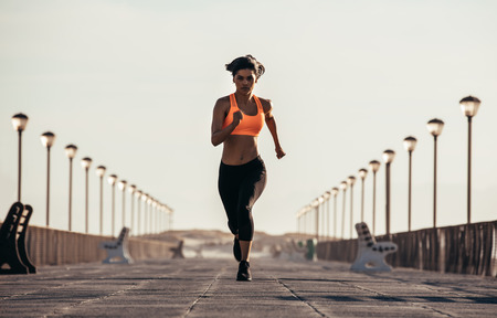 Woman runs on seaside boardwalk. Fit female athlete sprinting on seaside promenade in morning.