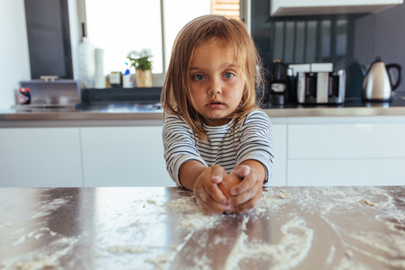 Innocent little girl breaks an egg with flour on the kitchen counter. Little girl baking in the kitchen at home.