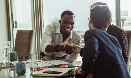 Businessmen discussing work sitting at conference table in office. Men shaking hands and smiling during a business meeting.