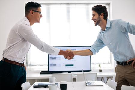 Geschäftskollegen Händeschütteln im Konferenztisch. Glückliche Geschäftsleute, die sich im Besprechungsraum begrüßen.