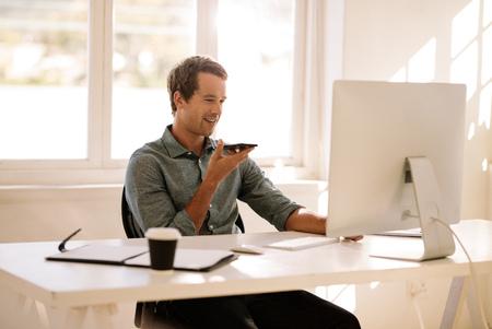 Mann, der Handy in der Hand hält und auf Lautsprecher spricht, der den Computer betrachtet. Geschäftsmann, der bequem von zu Hause aus arbeitet. Standard-Bild