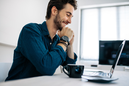 Software developer sitting in front of computer and working in office. Smiling man looking at laptop sitting with his chin resting on hands with a coffee cup on the table.