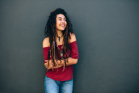 Portrait of a young curly haired woman wearing fashionable clothes and accessories standing against a wall. Smiling woman standing against a wall with arms crossed looking away. Stock Photo