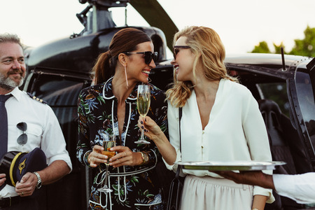 Cheerful female friends having wine outside a helicopter with pilot standing by. Women enjoying welcome drinks by a helicopter. Foto de archivo