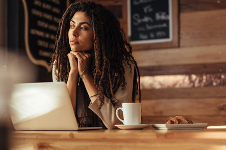 Woman entrepreneur sitting in a restaurant resting her chin on her hands thinking deeply. Freelancer sitting in cafe with coffee and snacks working on laptop computer.