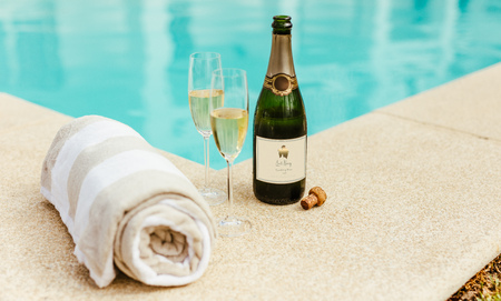 Two glasses of wine with bottle of sparkling wine and soft cotton towel on side of a swimming pool edge. Standard-Bild