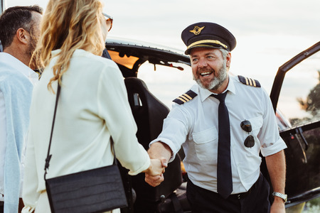 Helicopter pilot shaking hands with woman and smiling. Couple traveling through a private helicopter with pilot greeting them. Stock Photo