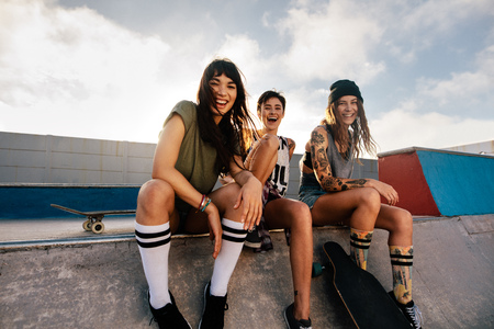 Portrait of happy young women sitting on ramp at skate park and smiling. Group of female friends at skate park. Archivio Fotografico - 101780254