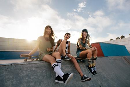 Group of women sitting on ramp in skate park. Female friends enjoying a day at skate park.