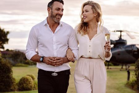 Pareja con una copa de vino caminando al aire libre con un helicóptero en segundo plano. Hombre y mujer con una bebida caminando juntos.