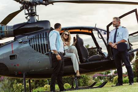 Beautiful woman getting down the helicopter with the help from her boyfriend. Couple disembarking their helicopter with pilot standing by. Standard-Bild