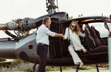 Piloot met de hand van een vrouw die uit de helikopter stapt. Rijke jonge vrouw reist door haar helikopter.