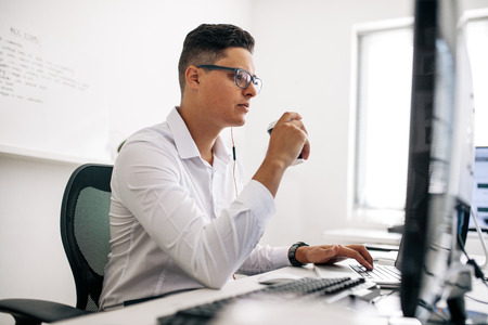 Smiling software developer sitting at his office desk working on laptop wearing earphones. Man wearing spectacles working on laptop computer in office and drinking coffee.