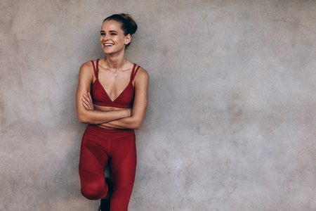 Smiling woman athlete in standing with her arms crossed and looking away. Sporty female standing against a grey wall.