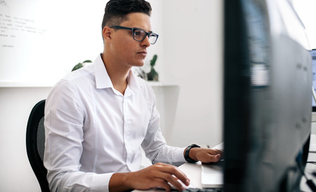 Software developer sitting in front of computer and working in office. Man wearing spectacles working on laptop and computer in office.