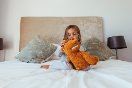 Cute little baby girl putting a crown on her teddy bear. Innocent girl child playing with her soft toy.
