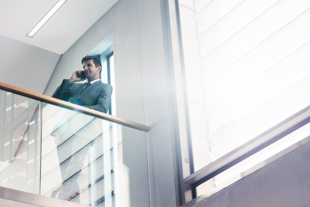 Low angle view businessman standing by railing and talking on mobile phone. Office manager making a phone call in office.