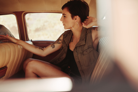 Attractive young woman sitting on the backseat of the car. Female traveling by a car. Stock Photo